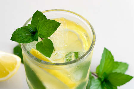 Fresh homemade cocktail with lemon, mint and ice on a white table, close up 免版税图像
