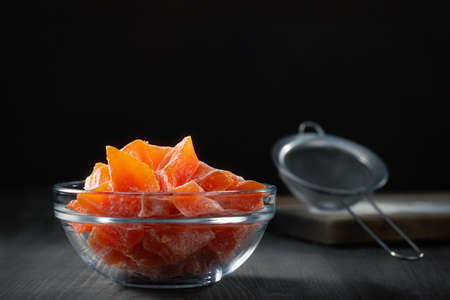 Natural farm homemade candied pumpkin fruits sprinkled with powdered sugar in a glass bowl on a wooden table
