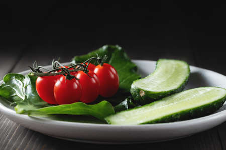 Fresh vegetables and herbs in a plate on a wooden table. Concept of vegetarianism and healthy eating