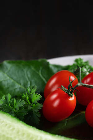 Fresh vegetables and herbs in a plate on a wooden table. Concept of vegetarianism and healthy eating. Copyspace.