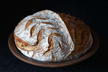 Homemade round dark bread with flour crust and painted spikelet on a clay plate