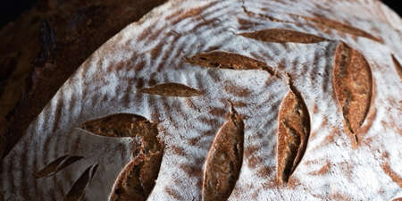 Homemade round dark bread with flour crust and painted spikelet close up on