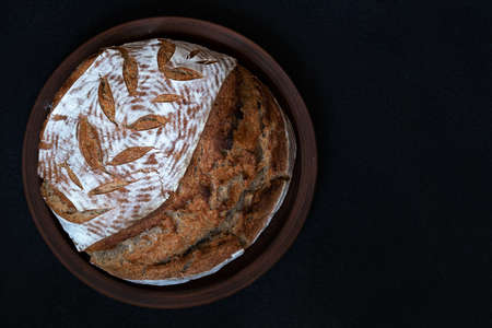 Homemade round dark bread with flour crust and painted spikelet on a clay plate. Top view with copy space