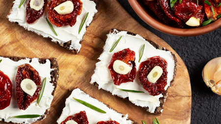 Homemade multigrain bread sandwiches with cream cheese and sun-dried tomatoes on a wooden platter. Healthy eating concept. Flat lay, topview 免版税图像
