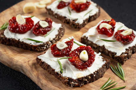 Homemade multigrain bread sandwiches with cream cheese and sun-dried tomatoes on a wooden platter, close-up. Healthy eating concept 免版税图像