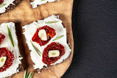 Homemade multigrain bread sandwiches with cream cheese and sun-dried tomatoes on a wooden platter. Healthy eating concept. Copyspace, flatlay, topview 免版税图像
