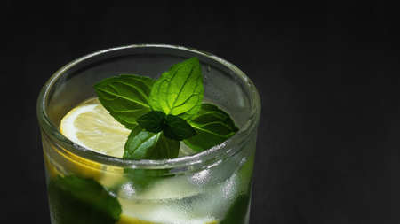 Fresh homemade cocktail with lemon, mint and ice on a dark background close-up 免版税图像