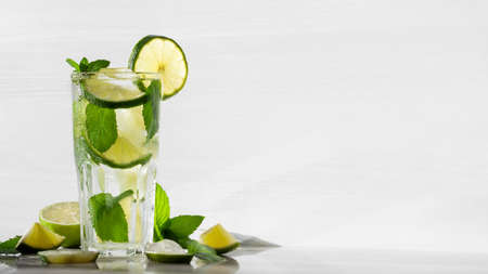 Fresh homemade mojito cocktail in a tall glass with lime, mint and ice on a white wooden background, copy space