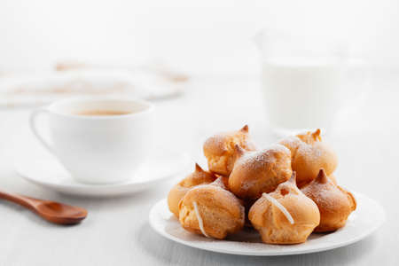 Morning coffee with cakes. Profiteroles, coffee, cream on a white wooden table