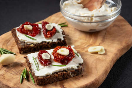 Homemade multigrain bread sandwiches with cream cheese and sun-dried tomatoes on a wooden platter. Healthy eating concept 免版税图像