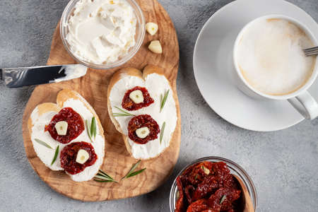 Homemade sandwiches with cream cheese and sun-dried tomatoes on a wooden board of olive - delicious healthy breakfast, italian cuisine, flat lay 免版税图像