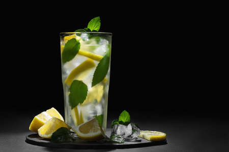 Fresh homemade cocktail with lemon, mint and ice on a dark background