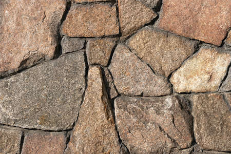 Stone wall of granite close-up, texture, background