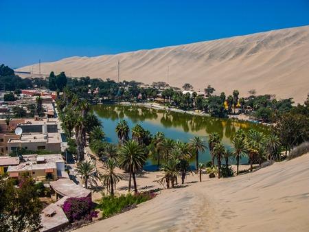 모래와 모래 언덕으로 둘러싸인 Huacachina 오아시스, 페루