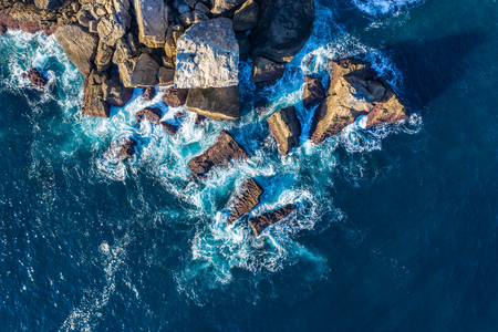 Detail of sea waves colors breaking in the coast of Lekeitio, Basque country - drone aerial view