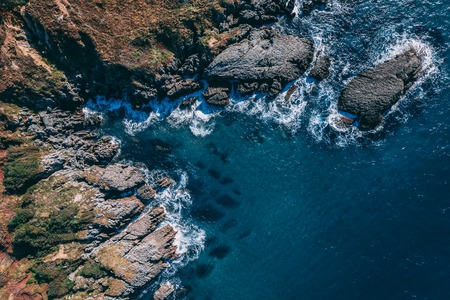 Detail of sea waves colors breaking in the coast of Sonabia, Spain, Cantabrian sea - drone aerial view