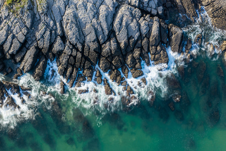 Sea waves breaking in the reefs and coast of Sonabia, Spain, Cantabrian sea - drone aerial view - long exposure