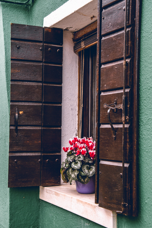 Red flowers in a window ledge in Murano, Italy