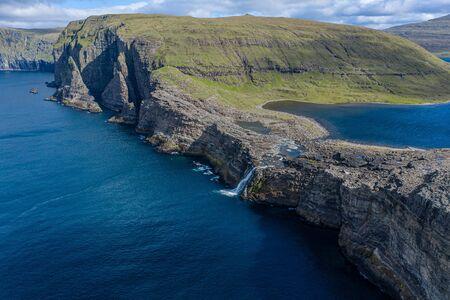 Bosdalafossur waterfall on Vagar island coastline aerial view, Faroe Islands