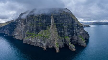 Aerial view of Trollkonufingur (Witch's Finger) Fjord under the clouds on Vagar island, Faroe Islands