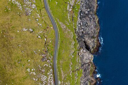 Road near the cliffs of Sandur in Sandoy island aerial view, Faroe Islands