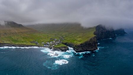 Natural harbour gorge in Gjogv village aerial view, Faroe islands Фото со стока