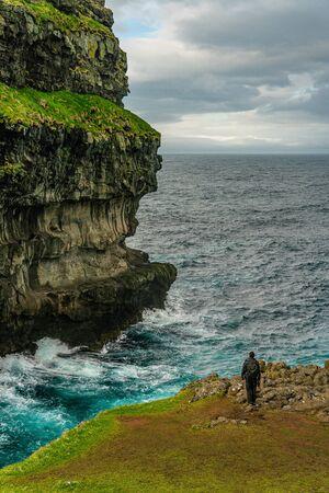 Unidentified tourist near Gjogv village cliffs in Eysturoy island, Faroe Islands
