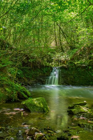 Sun ray lights over a small waterfall in a river in Galdames, Basque Country, Spain