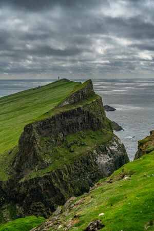 The lighthouse on Mykines island under the clouds, Faroe Islands