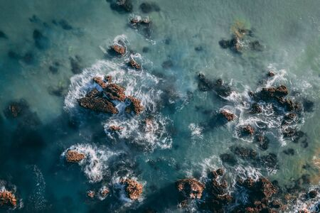 Sea waves breaking in the reefs and coast of Sonabia, Spain, Cantabrian sea - drone aerial view Фото со стока