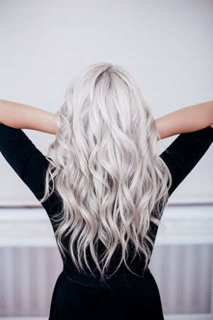 beautiful girl back with silver gray ash blonde curly wavy long hair in black dress isolated