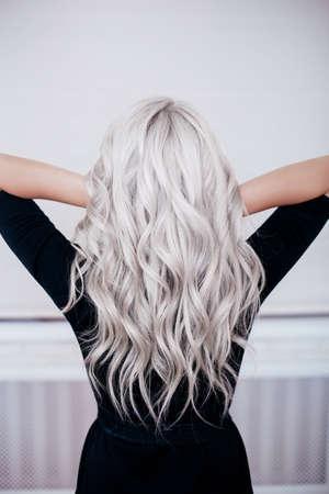 schönes Mädchen zurück mit silbergrauen, aschblonden, lockigen, gewellten langen Haaren im schwarzen Kleid isoliert