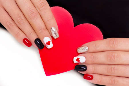 woman hands with beautiful creative red heart manicure nails for Valentines Day