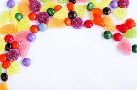 Scattered colored candy on a limited white background Foto de archivo