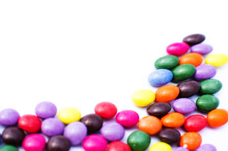 Scattered colored candy on a limited white background Stock Photo