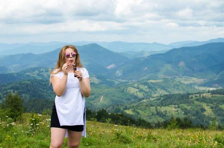 A young girl loves to travel and conquer the peaks of the mountains, she is happy
