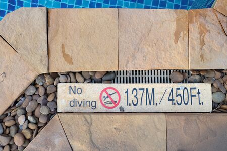 pool side: no diving sign at swimming pool side. show how deepness is in meter and foot measure. Stock Photo