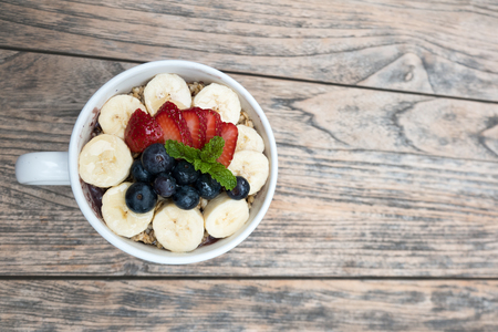 drupe: very delicious a small, round, black-purple drupe acai bowls with fresh fruit strawberry, blueberry, banana and peppermint leaves on top in cute white cup on the wooden table. this smoothie dessert is good for summer in Hawaii.