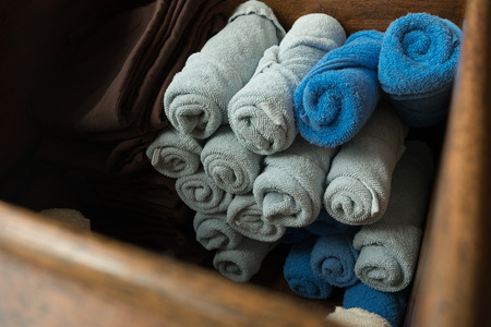 delightful: clean nice shape of light gray and blue rolled towel and brown comfort pants in the wooden box. they was prepared for welcoming guest and changing for Thai massage in spa resort business. feel cozy and delightful.