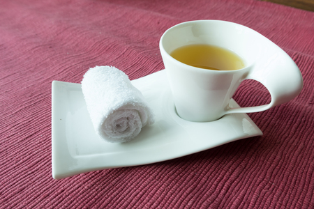 habitable: white scented rolled wet towel and hot Thai herb tea on to welcome a guest to thai aroma massage resort spa, Thailand. Stock Photo