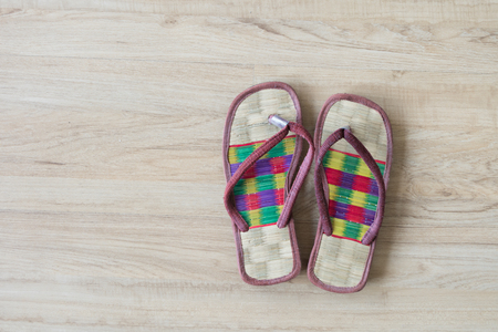 knoll: Thai local cozy weave sandal on wooden floor. slipper at home feel comfortable relax. knolling concept. Stock Photo