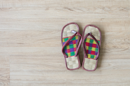 habitable: Thai local cozy weave sandal on wooden floor. slipper at home feel comfortable relax. knolling concept. Stock Photo