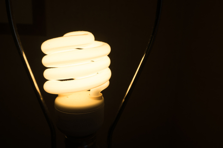 unclear: luminous Fluorescent Spiral lamp bulb turn on bright in dark place. like found idea from thinking in unclear situation, solve the problem or way to be creative and success