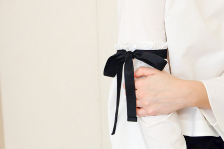 white sleeve: Woman hand on long white sleeve with black string bow tie style details. Close up trendy fashion. Stock Photo