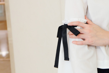 elbow white sleeve: Woman hand on long white sleeve with black string bow tie style details. Close up trendy fashion. Stock Photo
