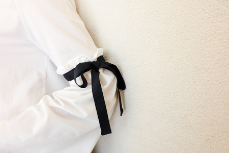 elbow white sleeve: long white sleeve with black string bow tie style details. Close up trendy fashion.