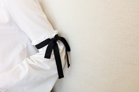 white sleeve: long white sleeve with black string bow tie style details. Close up trendy fashion.