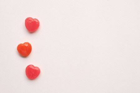 three Red Valentines day heart shape candy line on white paper background. Love Concept. Minimalism style. Knolling top view. Stock Photo