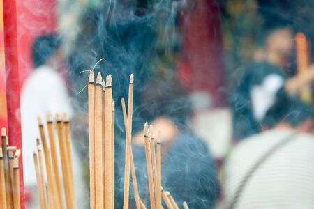 incense joss stick burning slowly with fragrant smell smoke. People praying on Chinese Buddhist temple on Chinese new year, Luna new year. Stock Photo
