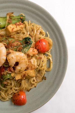 indo: Mie goreng, fried yellow noodle. with prawn seafood vegetable tomato choy egg garlic shallot onion shrimp cabbage on gray plate white table cloth. Deliciously famous indonesian Malaysian spicy dish.